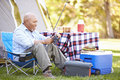 Senior man on camping holiday with fishing rod smiling Stock Photos