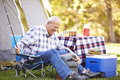 Senior man on camping holiday with fishing rod smiling Royalty Free Stock Images