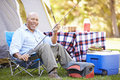 Senior man on camping holiday with fishing rod smiling to camera Stock Photos
