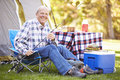 Senior man on camping holiday with fishing rod smiling to camera Royalty Free Stock Photography