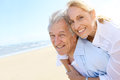 Senior man carrying his wife on his back on the beach men giving piggyback ride to Royalty Free Stock Image