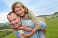 Senior man carrying his wife on his back men giving piggyback ride to Royalty Free Stock Image