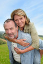 Senior man carrying his wife on his back men giving piggyback ride to Stock Photos