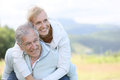 Senior man carrying how wife on his back men giving piggyback ride to woman Royalty Free Stock Image