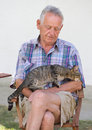 Senior man with cat tabby in his garden Stock Images