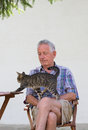 Senior man with cat tabby in his garden Royalty Free Stock Images