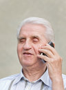 Senior man with cell phone talks on and smiles Stock Photography