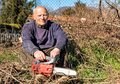 Senior man with chainsaw sitting to rest Royalty Free Stock Photo