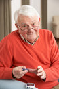 Senior Man Checking Blood Sugar Level At Home Stock Image