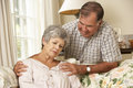 Senior man comforting unhappy wife at home Stock Photography
