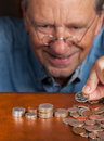Senior man counting cash into piles Royalty Free Stock Image