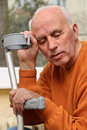 Senior man with crutch resting Stock Photo