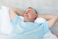 Senior man day dreaming in bed with hands behind head Royalty Free Stock Images