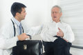 Senior man with doctor men talking about pain and symptoms to young male Stock Photos