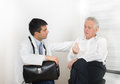 Senior man with doctor men talking about symptoms to young male Stock Image