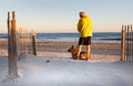 Senior Man with Dog Enjoying Morning on North Carolina Beach Royalty Free Stock Photo