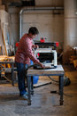 Senior man doing carpentry with edging plane on workbench carpenter working a wooden board planers woodworking shop workshop tools Royalty Free Stock Images