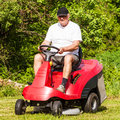 Senior man driving a red lawn mower in front of the trees during gardening activity Stock Photography