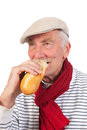 Senior man eating french bread portrait with cap and scarf Stock Photos