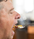 Senior man eating a spoon of vitamins Stock Photography