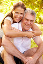 Senior man embraced by his adult daughter outdoors men Stock Images