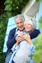 Senior man embracing his wife in the garden men at house front door Stock Image