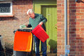 Senior man emptying trash or rubbish a his into a bin for collection by refuse Royalty Free Stock Photography