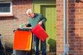 Senior man emptying trash, garbage or rubbish. Royalty Free Stock Photo
