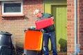 Senior man emptying trash,garbage  or rubbish. Royalty Free Stock Photo