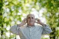 Senior man enjoying his music as he stands outdoors under the trees in the garden listening to headphones low angle view Stock Photo