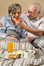Senior man feeding breakfast to woman couple lying in bed men Royalty Free Stock Images