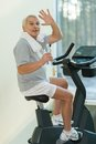 Senior man in a fitness club with bottle of water on bike Stock Image