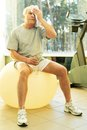 Senior man in a fitness club tired with towel on exercise ball Royalty Free Stock Image