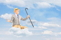 Senior man floating on a cloud and spreading arms against cloudy while holding cane sky Royalty Free Stock Images