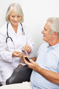 Senior man getting blood sugar measurement men with diabetes from doctor Royalty Free Stock Photos