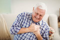 Senior man getting chest pain in living room Stock Image