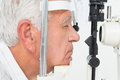 Senior man getting his cornea checked close up side view of a Royalty Free Stock Image