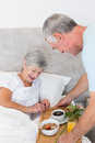 Senior man giving breakfast tray to wife in bed men happy at home Stock Photos