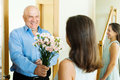 Senior man giving bunch of flowers to woman men women at home Royalty Free Stock Photography