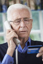 Senior man giving credit card details on the phone confused Stock Image