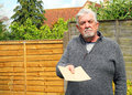 Senior man giving a plain brown envelope an angry look on his face Stock Images