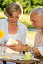 Senior man giving present to his wife elderly married couple opening together Stock Image