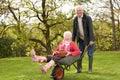 Senior Man Giving Woman Ride In Wheelbarrow