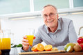 Senior man with a glass of orange juice Royalty Free Stock Photo