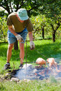 Senior man grilling chickens Royalty Free Stock Photo
