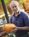 Senior man and halloween shopping one picking out pumpkin smiling at outdoor market looking at camera Royalty Free Stock Image