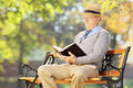 Senior man with hat sitting on a bench and reading a book outsid wooden outside Stock Photos
