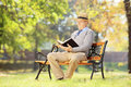 Senior man with hat sitting on a bench and reading a novel in a wooden park Royalty Free Stock Images