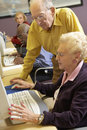 Senior man helping senior woman to use computer Royalty Free Stock Photo