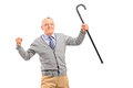 A senior man holding a cane and gesturing happiness looking at camera isolated on white background Royalty Free Stock Photos